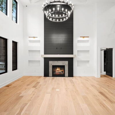 A touch of contemporary with wood flooring, shelved fireplace, modern staircase with multiple windows overlooking the backyard